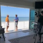 Crew films owners Dr. Lebron Lackey and Russell King on their beachfront balcony.